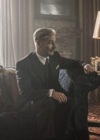 Still from The Crown showing Anthony Eden sat in a chair at Sandringham