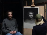 Sitter sat to the left of the picture and the artist and easel with portrait on to the right