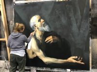 Artist to the left painting a large picture of bearded man