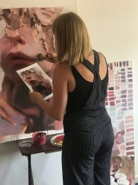 Female painting a face whilst looking at a smaller copy of face