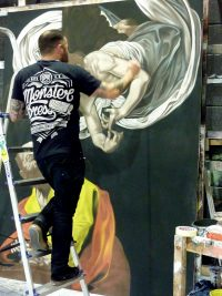 Artist stood on step ladder painting an angelic body