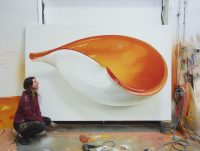 Artist knelt to the left of Large spray painting of white and yellow murano glass bowl