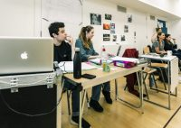 Two production arts students sat at table watching rehearsals. Teacher and other student sat at another table to their right watching rehearsals, and an acting student stood behind them