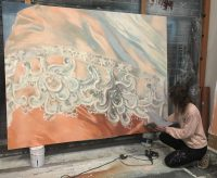 Artist knelt down to the right of large painting showing white and peach decor