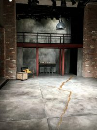 Stage with tea chest and chair to the left, table and stools at the back under metal bridge, crack on floor depicting earthquake