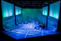 Empty stage decorated mostly in blue with ice painted on the floor, large snowflakes at the back and a drum kit on the right hand side