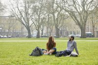 Two students sitting on the grass in Queen's Square
