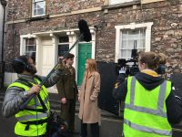 Image of actors and crew in the street wearing hi viz and stood around a camera
