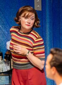 actress with short brown hair in a stripy top and red trousers