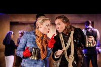 Two female actors stood very close together on stage both holding tankards