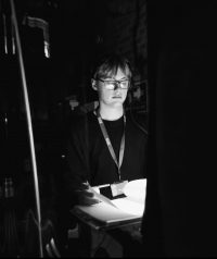 Black and white image of a stage manager, a man in black lothing lit by the desk light back stage