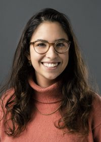 Headshot of female smiling at camera with dark brown hair, glasses and an orange roll neck jumper