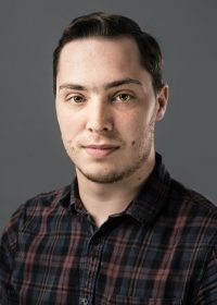 headshot of white male student with dark brown hair in a plaid shirt looking at camera