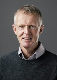 Headshot of man in grey jumper with shirt looking directly at the camera