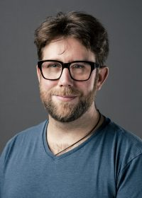 Headshot of man with black square glasses and brown hair and a beard looking directly at the camera