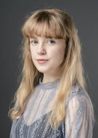 Headshot of woman with long blonde hair and a full fringe
