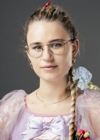 Headshot of woman with blonde hair in a side plait and glasses