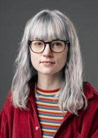 Headshot of woman in a red shirt with a stripey top, grey hair and glasses