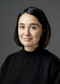 Headshot of female with short black hair, wearing a black top
