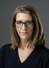 Headshot of woman with light brown hair and glasses wearing a black top