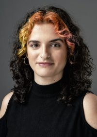Headshot of woman with curly black hair and orange highlights