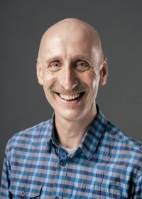 Headshot of smiling man who is bald wearing a checked blue top