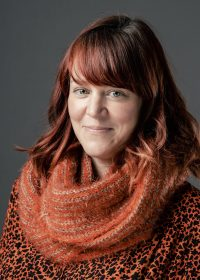 Headshot of woman with bright red hair in an orange scarf