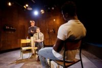 Two actors sat on chairs facing each other, one actor stood behind