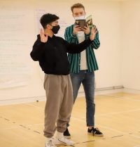 Two actors in rehearsal, one with arms outstretched, the other reading from Hedda