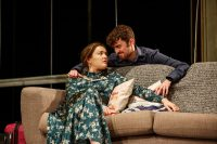 Actor sat on sofa and actor knelt behind sofa with his arm around her