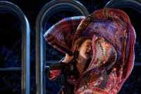 Actor on stage wrapping large patterned scarf around herself