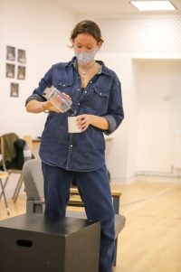 Actor stood pouring from a bottle into a mug