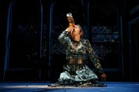 Actor knelt on floor drinking from bottle