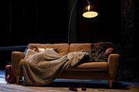 Two actors asleep on sofa
