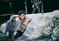 Actor sat on the floor behind rock