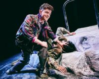 Two actors on stage, one led face down on the ground, the other knelt by him with his hand on the back of his head