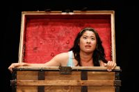 Actor sat in large wooden trunk with lid open, red lining