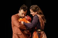 Two actors on stage in robes, holding a baby between them