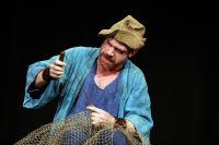 Male actor dressed as fisherman with fishing net