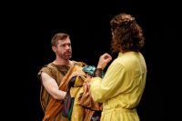 Two actors on stage, facing each other, both wearing robes