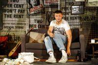 Actor sat on sofa, smoking, guitar and beer bottles around him