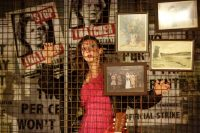 Actor stood on stage behind wired wall covered with old photos