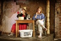 Two actors on stage, both sat at a small table, one drinking and one smoking