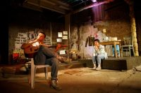 Actor sat in chair smoking and holding a guitar, another actor sat on stage with cup in hand