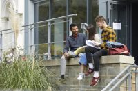 Three students sat on wall outside of BOVTS