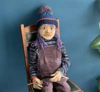 A life-size puppet of a girl with bobble hat and dungarees